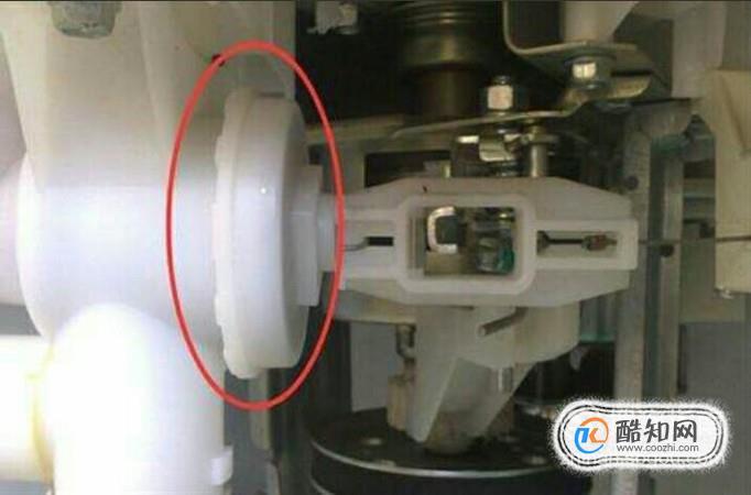 把洗衣机的后盖揭开, 拔出排水管,在橡胶电磁阀活塞出取出异物.图片