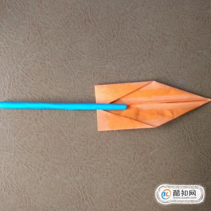 把橙色折纸涂上胶水,然后将蓝色圆柱放到中心粘住.